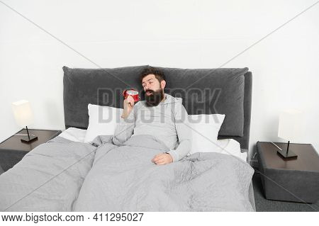 Tips For Waking Up Early. Man Bearded Sleepy Face Bed With Alarm Clock In Bed. What Terrible Noise.