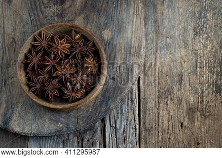 Anise Star. Stars In A Wooden Plate On A Brown Background. Fragrant Seasoning. The Bowl Is On The Ru