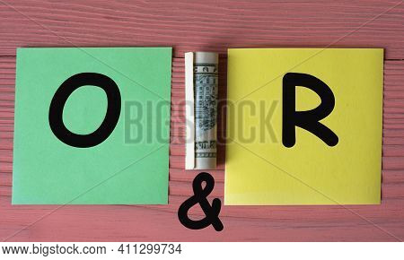 O&r - Acronym On Multicolored Pieces Of Paper On A Pink Wooden Background With A Banknote. Business