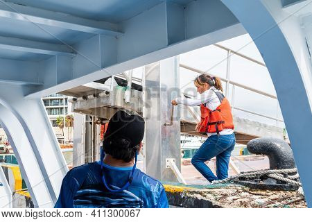 Cabo San Lucas, Mexico - October 13 2019: Female Worker Operates Marine Controls On Shore As Boat Ap