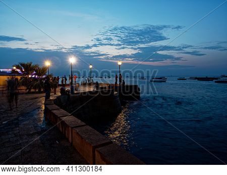 Stonetown (tanzania, Zanzibar Archipelago) In The Evening And Night. Streets And Harbour In Old Ston