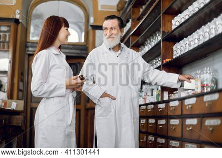 Two Professional Pharmacists, Senior Bearded Man And Young Woman, Working At Ancient Pharmacy. Male