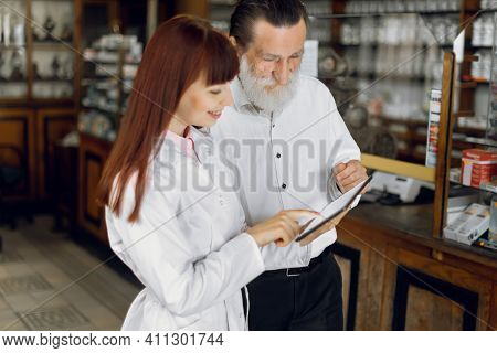 Young Professional Young Lady Pharmacist Holds Tablet And Consults Bearded Senior Man Customer In Ol