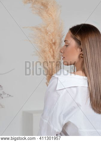Young Brunette In A White Shirt, A Stylish And Concise Portrait In Light Colors,