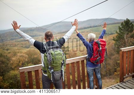 Hikers couple with raise arms, back view