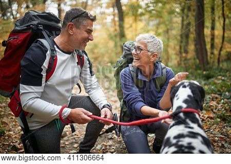 Senior couple in a squat with dog in nature