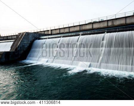 Long Exposure Panorama Of White Water Flowing Down Water Reservoir Lake Dam Sustainability Renewable
