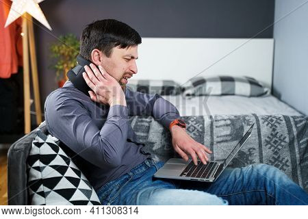 Tired Strained Man Suffering From Neck Pain While Working At Computer. Male Touchingly Massages Neck