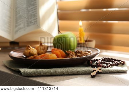 Dried Fruits, Apple, Prayer Beads, Bible And Candle On Window Sill Indoors. Great Lent Season