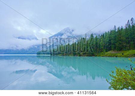 Berge und Kiefern Reflexion In einem Gletschersee