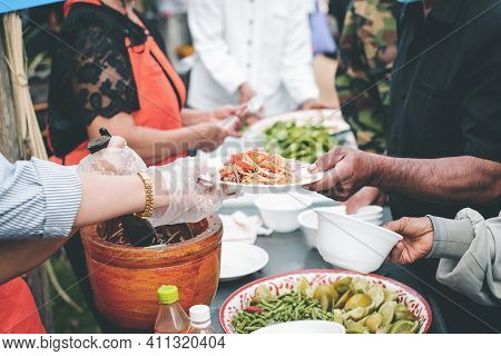 Volunteers Donating Food To People In A Society In Need Of Food: The Concept Of Helping With Food.