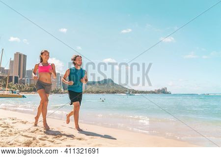 Hawaii running couple on Waikiki beach exercising outdoor in Honolulu city. Active healthy lifestyle.
