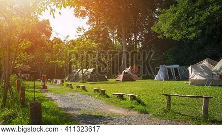 Morning Sunlight On Surface Of Various Field Tents Group On Green Lawn In Campsite Area At Natural P