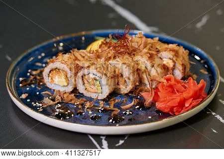 A Close-up Photo Of Fresh Sushi Rolls With Tuna Shavings, Philadelphia Cheese, And Eel On A Blue Cer