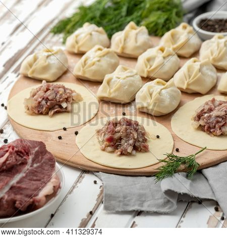 Raw Meat Filling On Rolling Dough Circles On Wooden Board. Process Of Cooking Dumplings. Ingredients