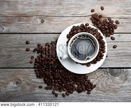 Coffee Beans And Cup Of Coffee On Old Wooden Table. Coffee In A White Cup.