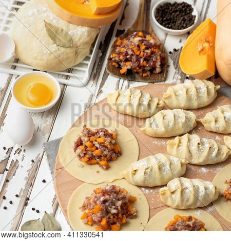 Pumpkin And Meat Filling On Rolling Raw Dough Circles. Process Of Cooking Dumplings. Top View. Ingre