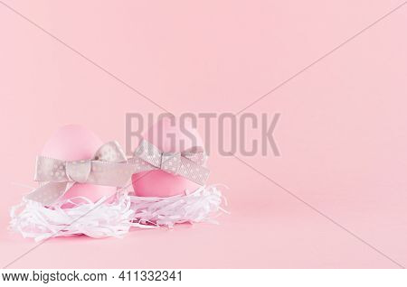 Simplicity Purity Easter Background - Pink Eggs With  Grey Bows In White Nest On Pastel Pink Color.