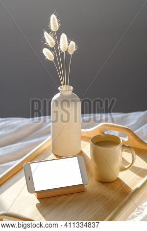 Wooden Tray Of Warm Cup Of Coffee, Smartphone Mockup, Vase Of Dried Flowers. Cozy Morning Breakfast