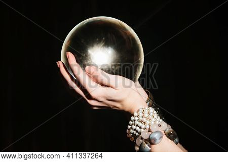 Fortunetellers Hands On A Glass Orb On Black Background. Prediction Of The Future