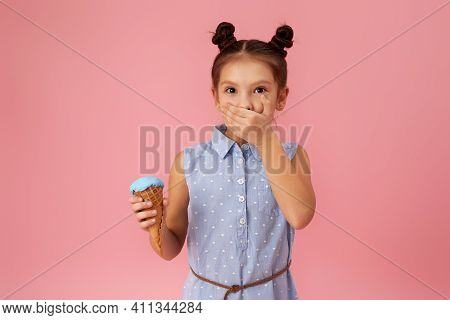 Little Girl Holding Ice Cream In Waffle Cone On Pink Background. Child With Sore Throat Touching Her
