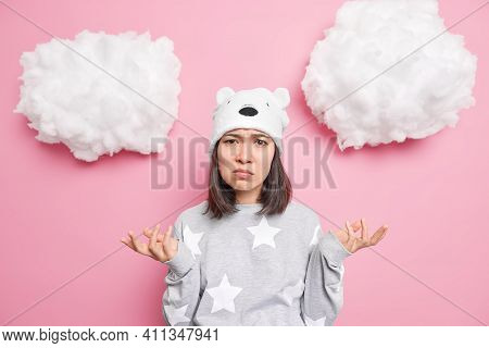 Questioned Unaware Brunette Asian Woman Spreads Hands Looks With Puzzled Hesitant Expression Wears P