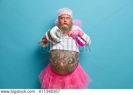 Photo Of Shocked Plump Bearded Man Pretends Being Fairy Of Purity Cleans Something Holds Bottle Of D