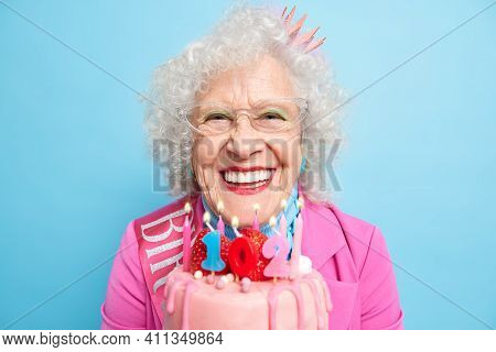 Horizontal Shot Of Positive Wrinkled European Woman Holds Birthday Cake Dressed In Stylish Clothes F