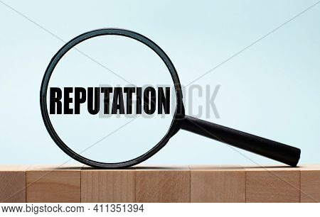 Cubes On A Light Blue Wooden Background. On Them A Magnifying Glass With The Word Reputation