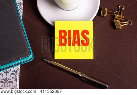 The Word Bias Written On Yellow Paper On A Brown Background Near A Coffee Cup And Diaries