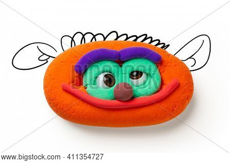 Animated plasticine cute face with eyes and smile on the white background. Monster face with drawn elements