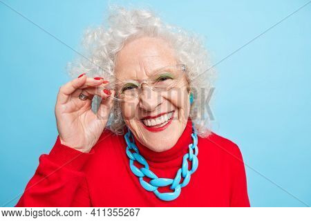 Portrait Of Positive European Woman Smiles Positively Keeps Hand On Rim Of Spectacles Wears Red Jump