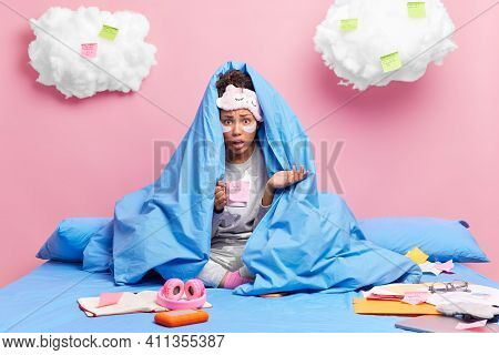 Puzzled Indignant Woman Poses Under Blanket Has Worried Excited Expression Because Of Deadline Drink