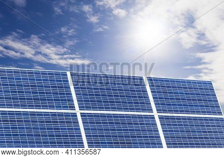 Blue Solar Panel Over Blue Sky, Sun And Clouds. Solar Panels Pattern For Sustainable Energy. Renewab