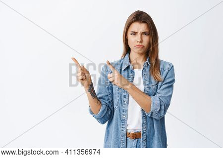 Angry Blond Girl Feel Unfair And Displeased, Pointing At Upper Left Corner And Frowning, Condemn Som
