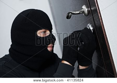 Thief Burglar force lock metal door with a tool during house breaking poster