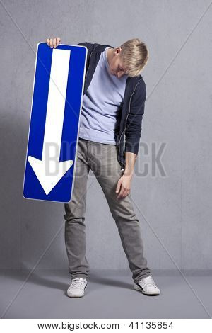 Upset man holding direction arrow sign pointing down with space for text isolated on grey background.