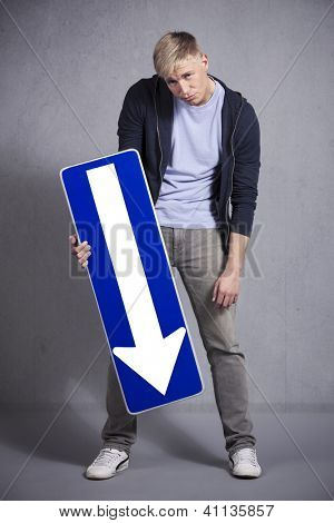 Unhappy man holding direction arrow sign pointing down with space for text isolated on grey background.