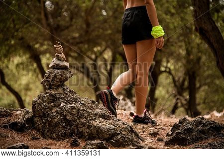 Close-up Cairn Marking Hiking Trail In Clearing In Pine Forest And Woman Walks At Background