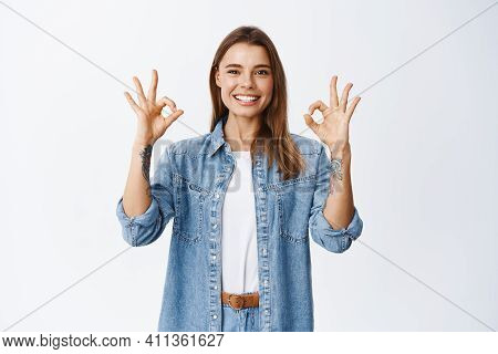 Portrait Of Smiling Young Woman Approve Good Product, Showing Okay Alright Sign And Looking At Camer