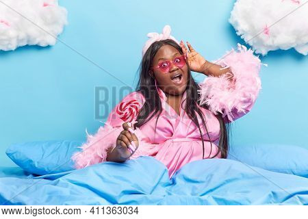 Dark Skinned Obese Woman Wearrs Trendy Sunglasses And Dressing Gown Holds Tasty Lollipop On Stick Ej