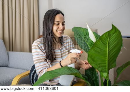 Long Haired Brunette Woman Takes Care Of Flowers And Smiles In Her Living Room Plant Care Concept