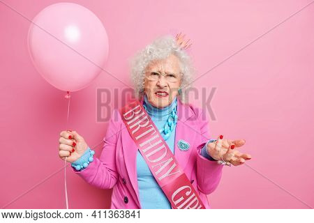 Puzzled Indignant Wrinkled Woman Celebrates Birthday Wears Festive Outfit Princess Crown On Head Hol