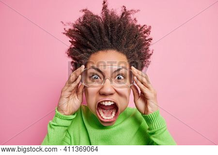 Outraged Afro American Woman With Hair Raised Up Screams Loudly From Anger Being Super Emotional And