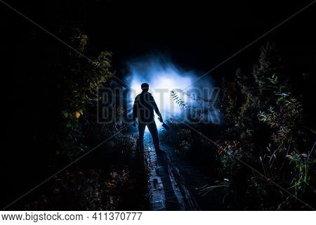 Strange Light In A Dark Forest At Night. Silhouette Of Person Standing In The Dark Forest With Light