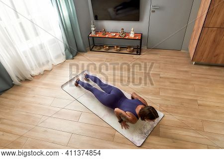 Top View Of Young Woman In Bodysuit Exercising, Doing Four Limbed Staff Yoga Pose On A Mat In Living