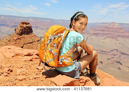 Grand Canyon hiker woman resting portrait. Hiking multiethnic girl relaxing on South Kaibab Trail, south rim of Grand Canyon, Arizona, USA.