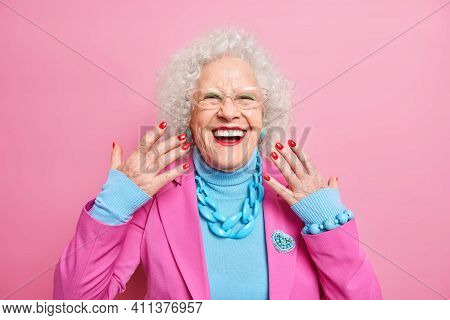 Portrait Of Elderly Curly Haired Woman Raises Hands Smiles Broadly Wears Spectacles Fashionable Outf