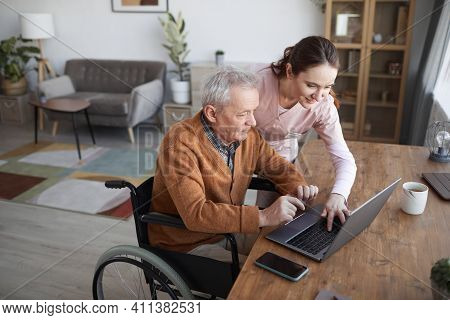 Portrait Of Senior Man In Wheelchair Using Laptop At Retirement Home With Nurse Assisting Him, Copy
