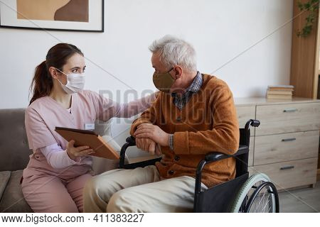 Portrait Of Young Nurse Assisting Senior Man In Wheelchair Using Digital Tablet At Retirement Home,